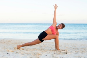 Woman having a relaxed yoga practice at the beach